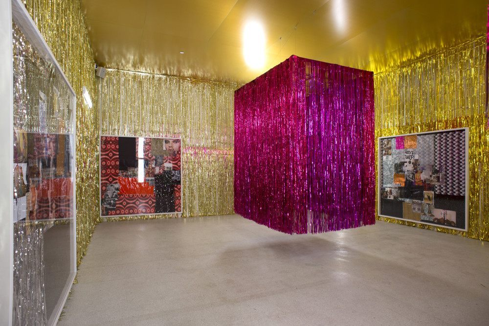The image shows a rectangular tall gallery space. The walls of the gallery are covered in long strands of gold tinsel, from ceiling to floor. On each of these walls hangs a large white frame filled with collaged photographs of people, landscapes and patterns cut from magazines. In the centre of the room a large rectangular curtain of bright pink tinsel is suspended from the ceiling, floating like a large glitzy rectangular structure with a three dimensional appearance.