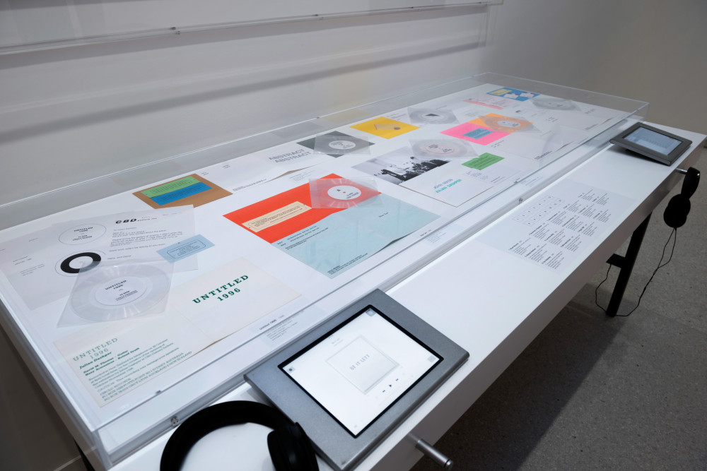 The image shows a long, white vitrine table filled with ephemera. Items in the vitrine include vinyl records and covers in a variety of bright neon colours. In front of the table are two small interactive touchscreens and a pair of headphones.