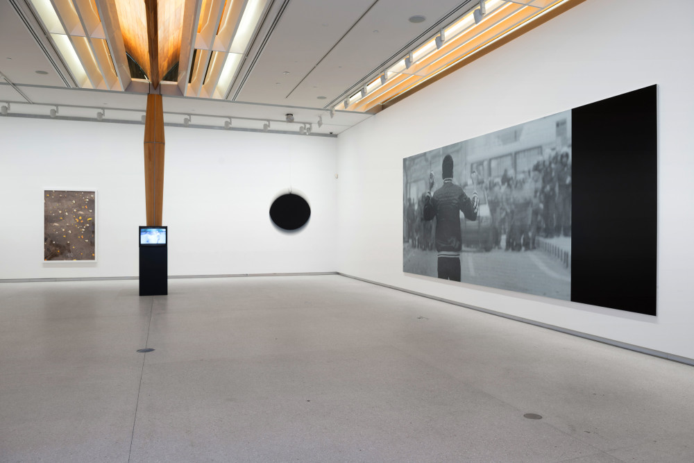 The image shows the corner of a gallery room. On the left hand wall, far left, is a tall framed photograph depicting orange peels scattered across dark grey tarmac. To the right of the photograph in front of a tall wooden column is a small cube television set on a plinth, playing a blue tinted film. To the right of this in the corner is a large black sphere attached to string, which is moving in an agitated manner. On the right hand wall hangs a large horizontal photograph in black and white of a man with his back to the viewer, facing a crowd of people and a stationary car in a street.