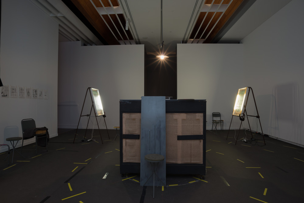 The image shows a large dimly lit gallery space. In the centre of the space stands an upright piano, facing away from the viewer so that its unpainted wooden back is exposed. At the other end of the room on each side of the piano stand two easels, which each hold neon lightboxes with headphones next to each. The floor of the space is covered with pieces of yellow tape which circle the installation multiple times. Some small drawings in plastic protectors are pinned to the left hand gallery wall, with chairs below them.